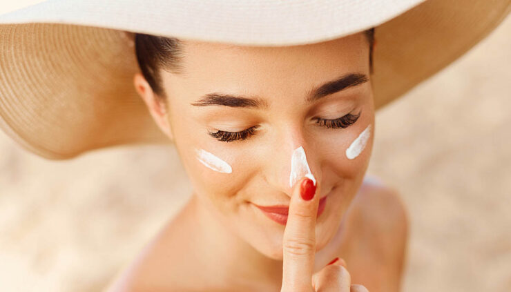 Woman wearing a hat and applying sunscreen